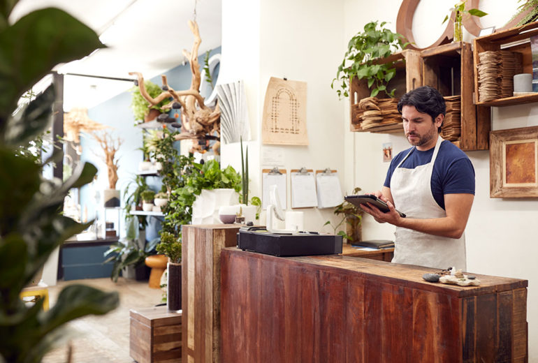 Male Owner With Digital Tablet Standing Behind Sales Desk Of Florists Store