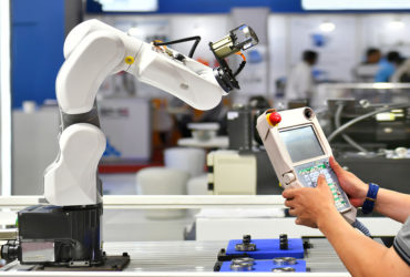 Engineer check and control automation Robot arm  in factory.