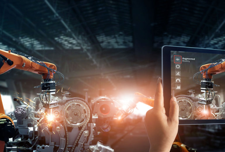 Augmented reality industry concept. Hand holding digital tablet use AR application to check and control welding robotics automatic arms machine in intelligent factory automotive industrial with monitoring system software. Digital manufacturing operation.