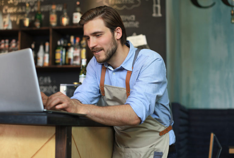Restaurant manager working on laptop, counting profit.