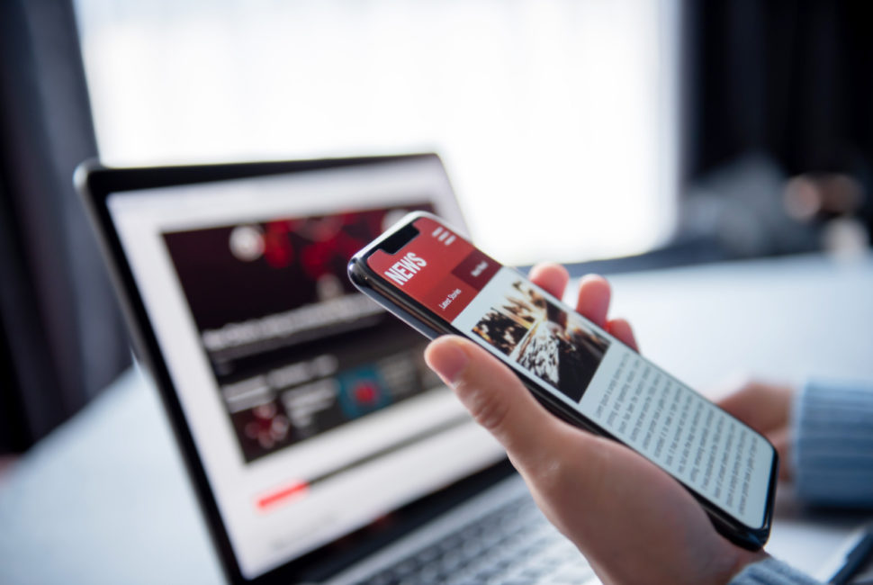 Online news on a smartphone and laptop, Woman reading news or articles in a mobile phone screen application at home. Newspaper and portal on internet.
